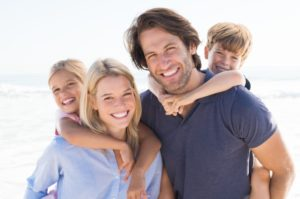 family of four smiling and embracing