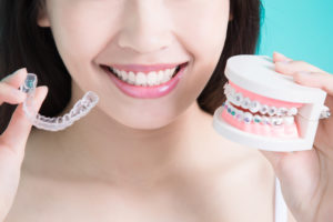 woman comparing conventional braces and invisalign