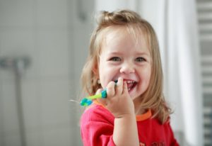 little girl holding toothbrush