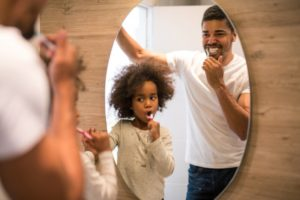 Father and daughter brush teeth together in front of mirror
