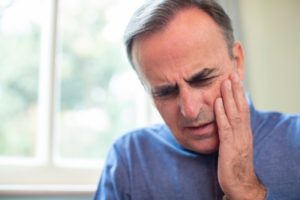 Man with hand on face wonders if it's a dental emergency