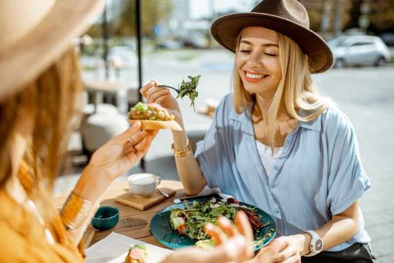 Woman smiling while eating lunch with friend