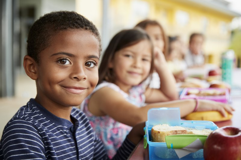 Kids smiling while eating lunch together